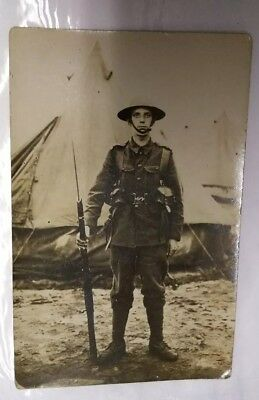 WW1 SOLDIER WITH RIFLE. Impression of writing on front of card.  RP POSTCARD.