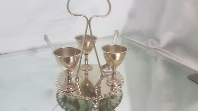 A vintage 3 settings silver plated egg cup set with stand and spoons.