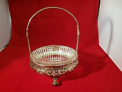 An antique silver plated butter dish on clawed legs with a glass insert dish.