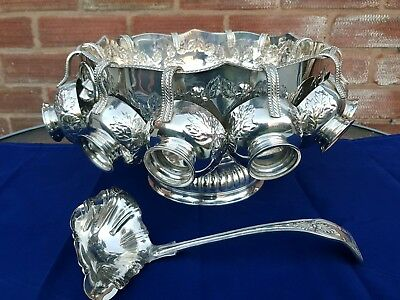 A fabulous antique floral embossed punch bowl.12 cups and ladle.very collectable