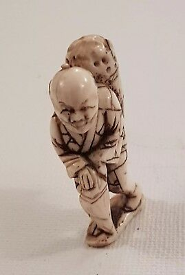 A meiji period Netsuke of farmer carrying a basket on his back & holding another