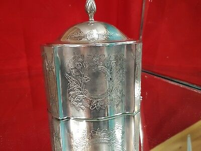 a silver plated tea caddy with engraved patterns.acorn finial.very ornate.