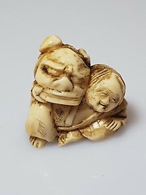 A Meiji period Netsuke of a resting Shishi-mai dancer holding his lion mask.