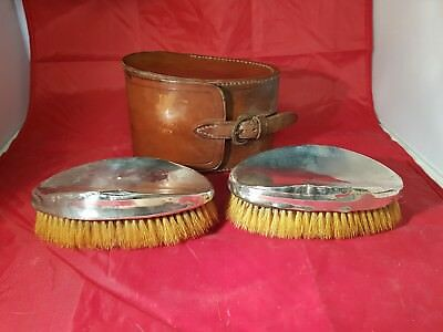 a pair of solid silver grooming brushes in original leather pouch.birmingham1922