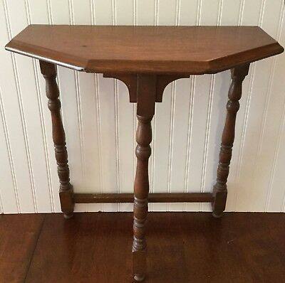 Small console table.  three legged table in half hexagon shape. Spindle legs.