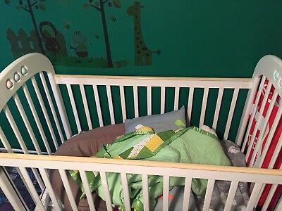 White cot with mobile