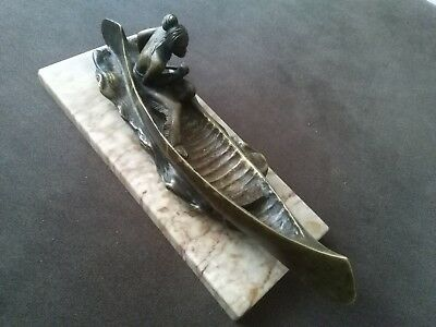 Antique cast bronze figure of a North American Indian in a canoe, 32cm long