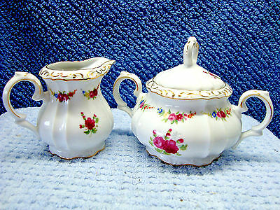 Floral and white porcelain sugar and creamer  with gold trim.