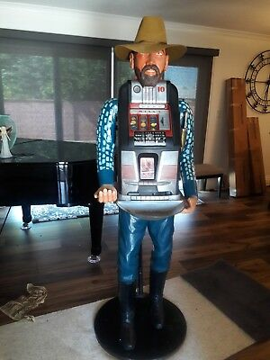 Wood carved cowboy statue with Mills 10 cent slot machine, collectibles.
