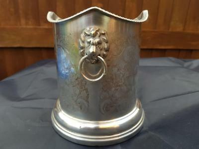 a very elegant antique silver plated wine bottle coaster with lions faces.