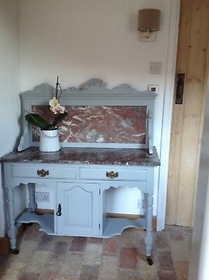 Antique washstand with ornate marble top and back