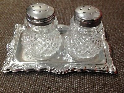 Small glass salt and pepper shakers on silver tray
