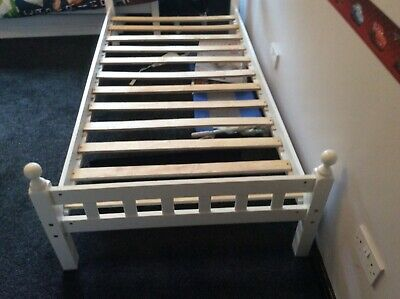 single white bed frame with wooden slats as base.