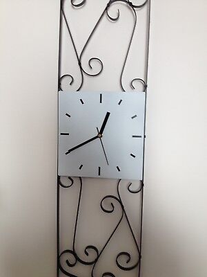 Wall Clock In Black Scroll Metal Wall Art Frame with a White Square Clock Face.