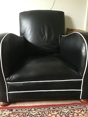 Art deco style black leather sofa and two chairs with wooden round feet.