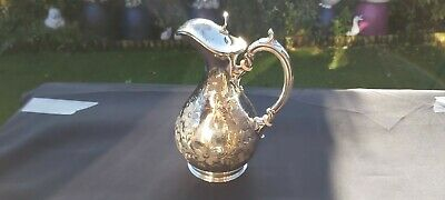 An Antique Silver Plated Water Jug With Engraved Patterns.by philip ashberry.