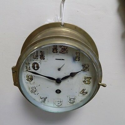 A brass cased ship's clock with white enamel dial and gilded Arabic numerals
