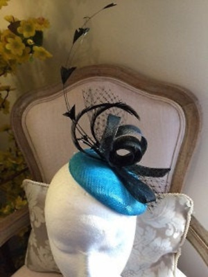 Beautiful turquoise blue fascinator base with black loops, netting and feathers.