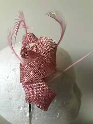 Pink loop fascinator with biot feathers on a silver headband.