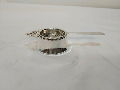 A Vintage Silver Plated Tea Strainer And Drip Bowl with elegant patterns.