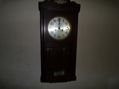 Vintage retro old wooden pendulum wall clock in cabinet , circa 1927
