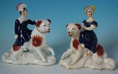 Pair Staffordshire children seated on dogs