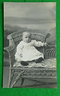 An Old Photo Postcard of a Baby on Wicker Couch