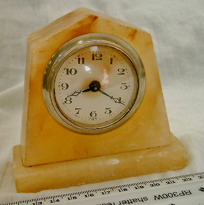 Small clockwork mantel clock in a marble surround