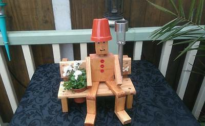 Wooden flowerpot man on bench planter with garden solar light