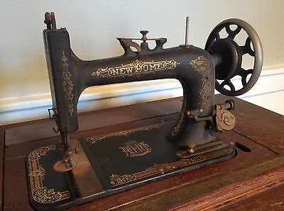 antique treadle sewing machine New Home brand. Oak cabinet. pickup only