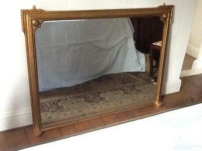 Over mantle plate glass mirror with wooden frame in gilt finish.