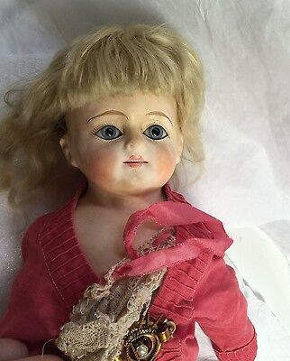 Antique bisque doll with straw stuffing