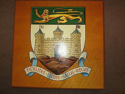 A vintage hand painted coat of arms on wooden panel