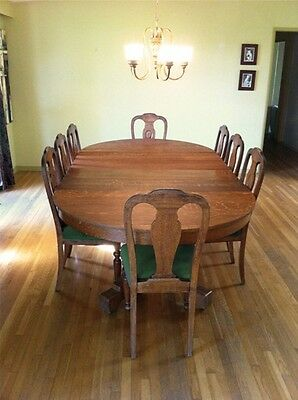 "Oak Antique 54"" round table with eight chairs and four leafs total length 102"""