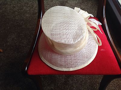 ladies cream hat with loop design and feathers. good for wedding or day at races