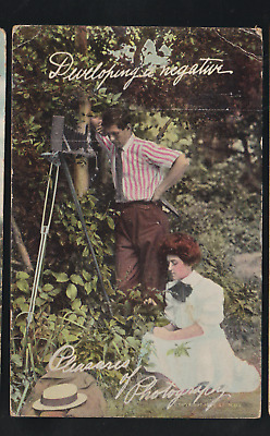 Comic/ romantic/ man taking pictures/ old camera/ lady posing in grass/postcard