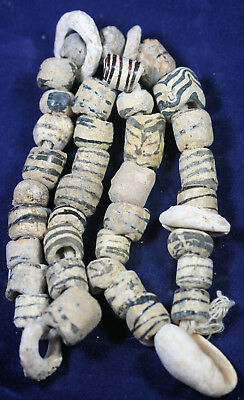 A collection of ancient white and black glass and shell beads