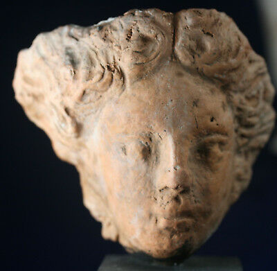 Large pottery head fragment mounted on a wood block