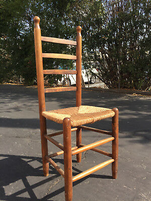 Three ladderback chairs with rush seats and curved back detail,