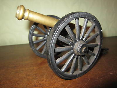 An old brass desktop cannon with cast iron carriage and wheels