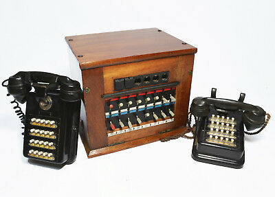 Antique telephone exchange switchboard with two phones, 1950s