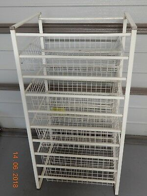 Free standing basket storage rack.  White metal with wire baskets on slides