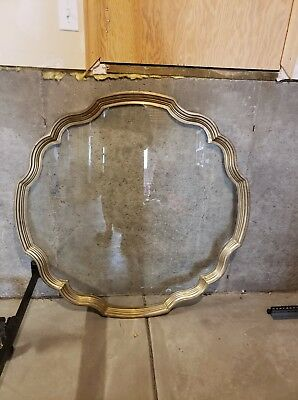 Vintage glass top coffee table with brass ring. Hollywood Regency style
