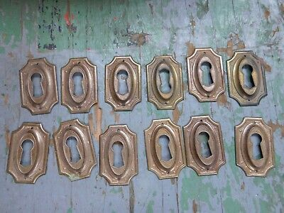 Twelve (12) vintage pressed brass keyhole covers escutcheons