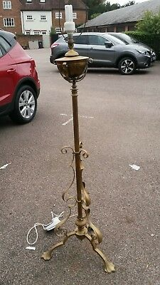 A brass standard lamp in Victorian style.