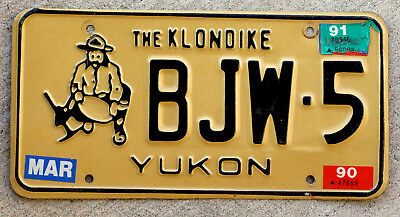 """Black on Tan Yukon """"The Klondike"""" License Plate with a 1990 and a 1991 Sticker"""