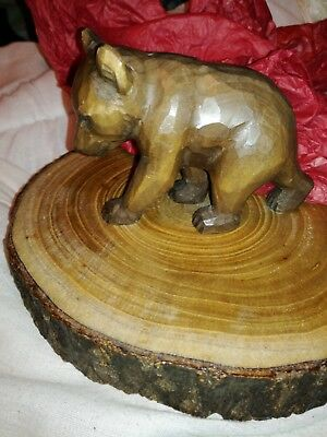Black forest style carved bear on a log