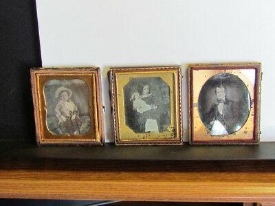 group of worn daguerreotype photographs including little girl with doll