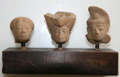 Three pottery heads on a wood stand