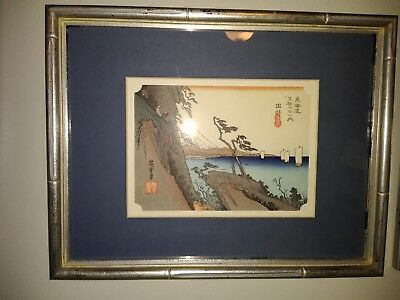 Antique Japanese wood block print of water, clifs and Mount Fugi.